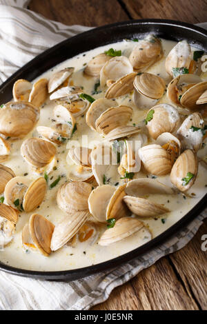 Stewed clams in creamy sauce with herbs close-up on a plate. horizontal - Stock Photo