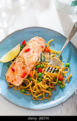 Chilli salmon with pasta and vegetables and lime wedge - Stock Photo