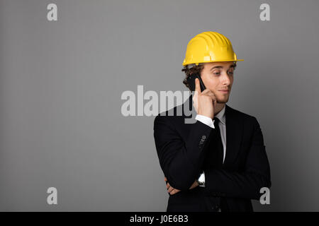 elegant man in suit with yellow protection helmet on gray background with empty space htalking at cellphone and - Stock Photo