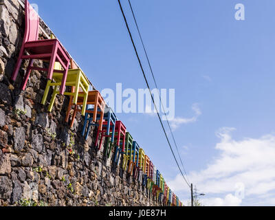 Coloured Chairs on a Stone Wall. A long line of wooden chairs, painted bright primary colours edges a rough stone - Stock Photo