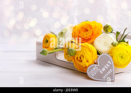 Close up of a bouquet of yellow ranunculus and a wooden heart with message Home sweet home - Stock Photo