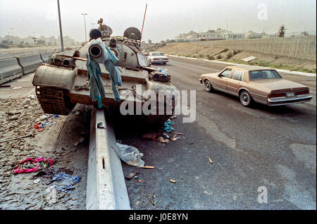 Cars drive past a destroyed Iraqi Army T-72 tank left behind by retreating soldiers following the liberation of - Stock Photo