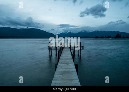 Cloudy sky over mountains, silhouette standing on dock, Lake Te Anau, Southland, New Zealand - Stock Photo