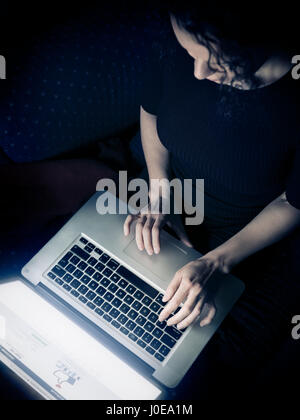 Woman using a laptop computer at home, overhead view, Facebook login page on display - Stock Photo