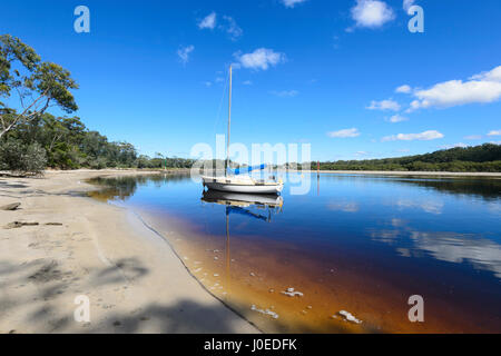 Sailing Boat moored in tannin-stained Currambene Creek, Huskisson, South Coast, New South Wales, NSW, Australia - Stock Photo