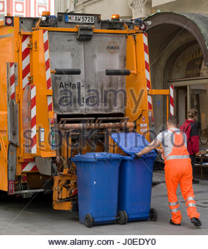Europe, Germany, Bavaria, Munich, View Of Dustbin Man Emptying Blue Plastic Trash Cans Into Orange Rubbish Truck - Stock Photo