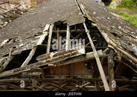 Damaged corrugated asbestos roof on old abandoned industrial building. - Stock Photo