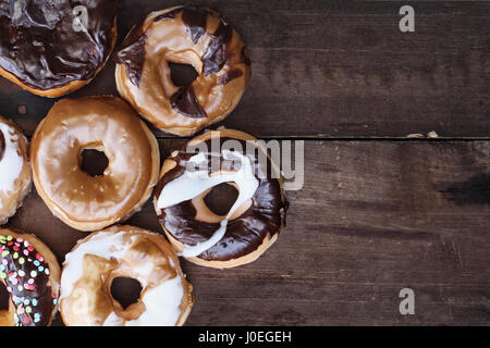 Background of chocolate, carmel, glazed and filled donuts over a rustic background with copy space. Image shot from - Stock Photo