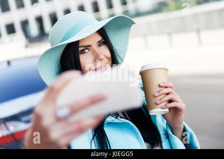 Woman in hat takes pictures - Stock Photo