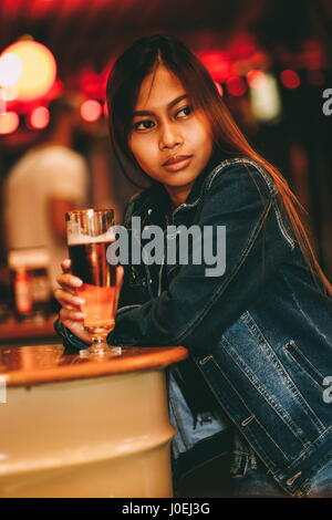 Young beautiful woman drinking beer in a bar - Stock Photo