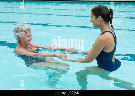 Side view of female coach helping senior woman in swimming pool - Stock Photo