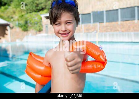 Young boy showing thumbs up at poolside in leisure center - Stock Photo