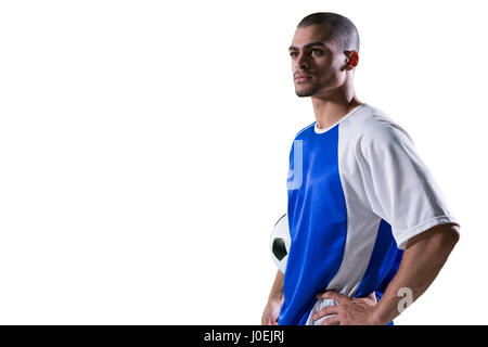 Football player holding football against white background - Stock Photo