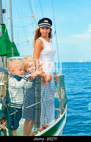 Happy family - mother in captain cap, baby son, daughter on board of sailing yacht. Children have fun discovering - Stock Photo