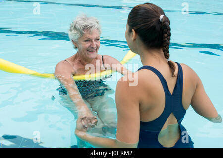 Smiling female coach helping senior woman in swimming pool - Stock Photo