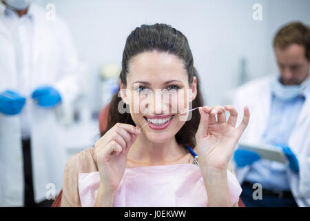 Female patient flossing her teeth at dental clinic - Stock Photo