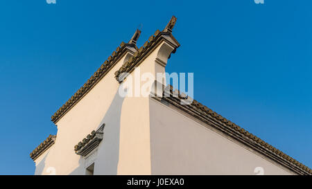 horse head wall with black tiles and bricks on wall top of traditional Chinese Anhui architecture used for separation - Stock Photo