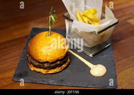 Burger with mushrooms, chili, mayonnaise and tomato. - Stock Photo