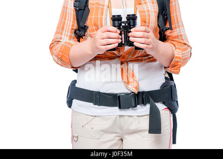 Hands of the traveler holding binoculars against the background of an orange shirt close-up - Stock Photo