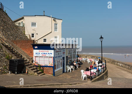 People eating outside or al fresco outside a the Lifeboat Cafe Cromer Norfolk UK on a sunny day - Stock Photo