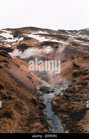 steam rises from a geothermal hot spring in Reykjadalur, a popular hiking trail near Reykjavik, Iceland - Stock Photo