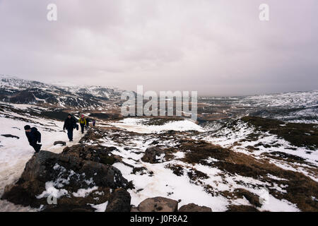 Hikers on the mountain trail near the geothermal hot springs of Reykjadalur, a popular tourist destination close - Stock Photo