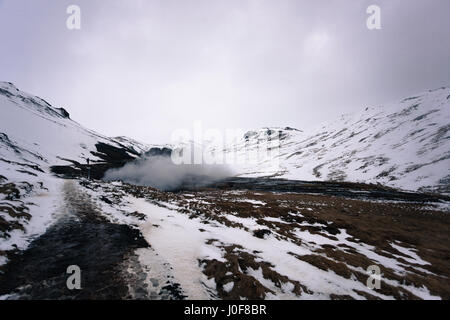 A plume of steam rises from the geothermal hot springs of Reykjadalur, a popular hiking trail in the mountains near - Stock Photo