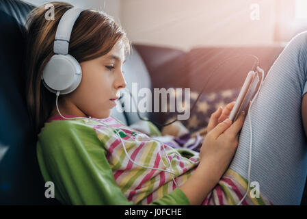 Girl sitting on black sofa using tablet and listening music - Stock Photo