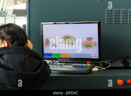 An X-ray monitor at airport and woman from security service. - Stock Photo