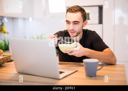... Man Eating Breakfast Using Laptop, Man In Kitchen Drinking Coffe    Stock Photo