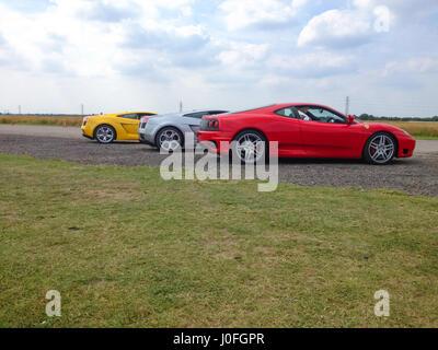 Three Super Sars - Red Ferrari 488, Silver Lamborghini Murcielago, Yellow Lamborghini Murcielago - Stock Photo