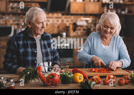 portrait of smiling senior couple making salad together in kitchen - Stock Photo