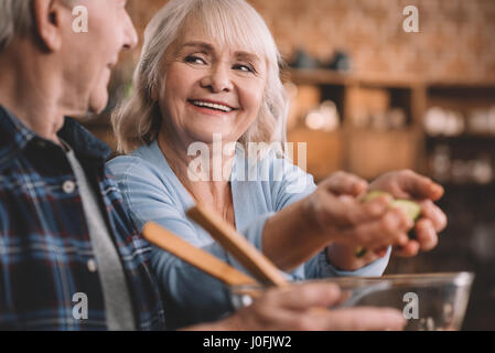 portrait of happy senior couple making salad together in kitchen - Stock Photo