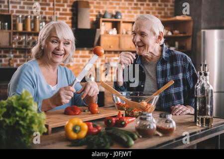 Happy senior couple cooking together and having fun at kitchen - Stock Photo