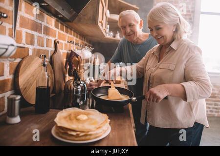 senior couple cooking pancakes on kitchen at home - Stock Photo