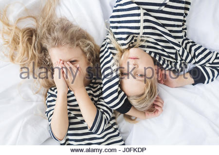 girl with white curly hair in a striped vest and a  boy with blond hair in a striped vest sleeping in bed. Children - Stock Photo