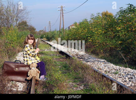little girl sitting on suitcase and waiting for train - Stock Photo