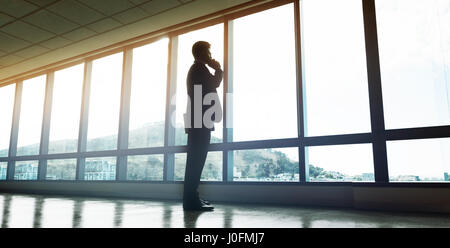 Full length of entrepreneur standing by window and talking on mobile phone. Man looking outside the office window - Stock Photo