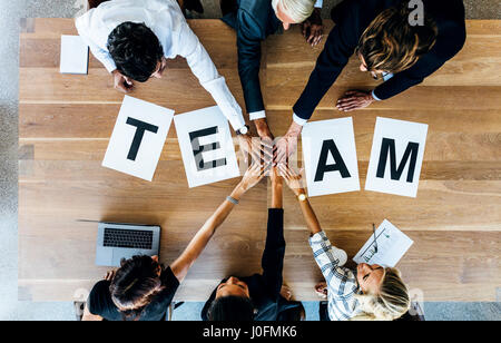 Group of business people putting their hands together over a table with work team. Top view of business team stacking - Stock Photo
