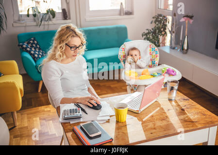Mother wearing eyeglasses working at home office on laptop and taking care of her baby - Stock Photo
