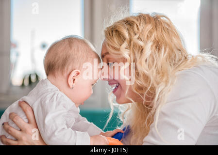 Mother and her baby head to head - Stock Photo