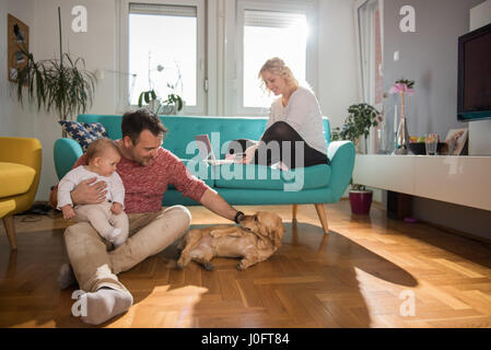 Father sitting on the floor and with baby in his arms playing with dog while wife sitting on sofa and doing online - Stock Photo
