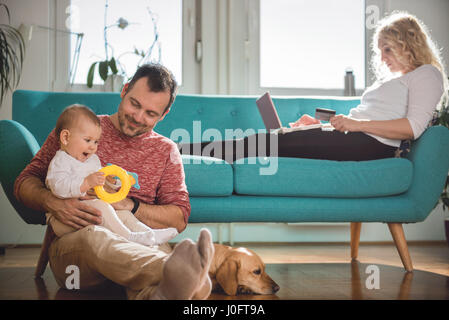 Father sitting on the floor and holding baby in his arms while wife sitting on sofa and doing online shopping with - Stock Photo