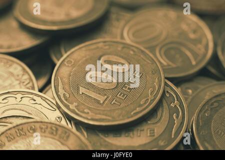 Many hundreds of tenge of coins, Kazakhstan money. Sepia tone of the photo. - Stock Photo