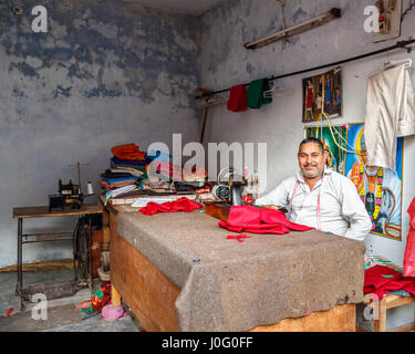 Friendly local Indian tailor working at a traditional sewing machine, Pragpur, a heritage village in Kagra district, - Stock Photo