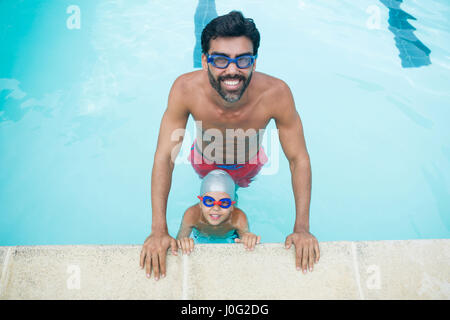 Portrait of father and son wearing swimming goggles in pool at leisure center - Stock Photo