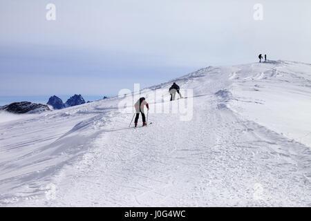 Skiers on ski slope at wind day. Caucasus Mountains, Georgia, ski resort Gudauri. - Stock Photo