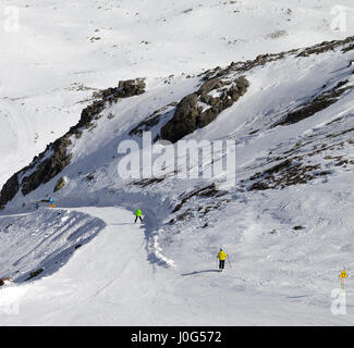 Snowboarders and skiers on groomed slope. Caucasus Mountains, Georgia, ski resort Gudauri at nice day - Stock Photo
