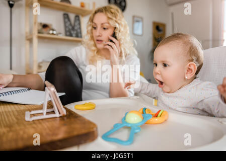 Excited baby watching smart phone while mother talking on smart phone and writing down notes at home office - Stock Photo