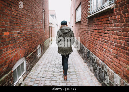 Lonely female person walking in the street, photographed from behind
